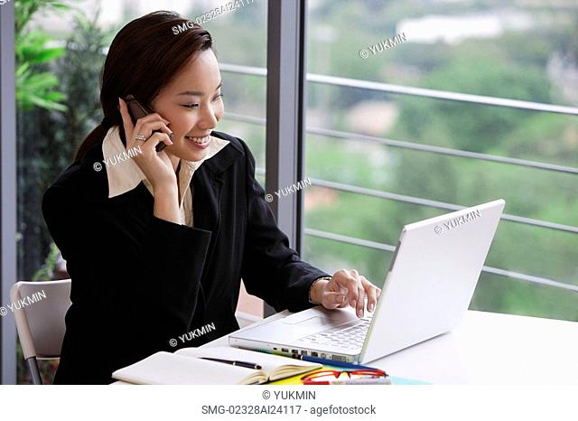 businesswoman at laptop with cell phone