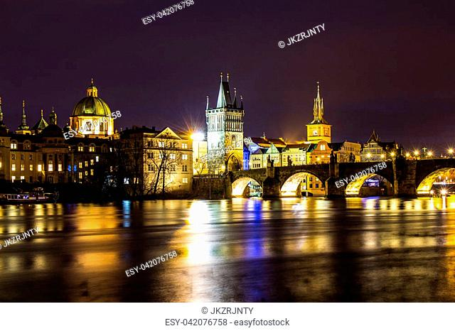 Beautiful night view of the Charles Bridge, the Old Town Bridge Tower, and the Old Water Tower, the Smetana Embankment and the Prague Beer Museum in Czech...