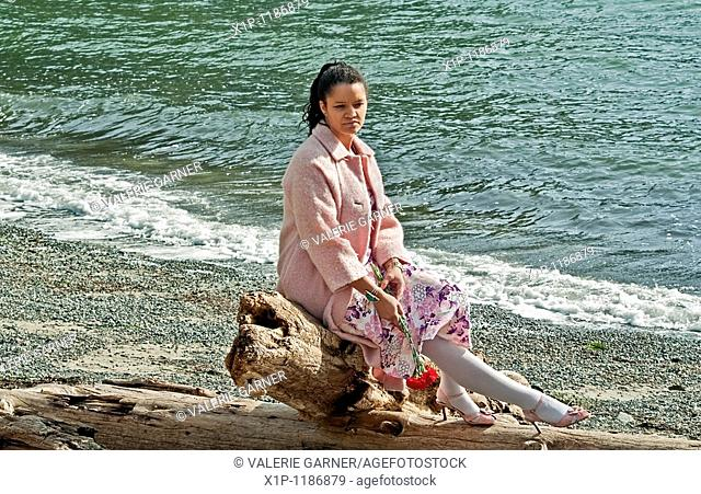 This pretty multi ethnic woman conveys many emotions, sadness, dejected, lonely as she's sitting on driftwood at a beach