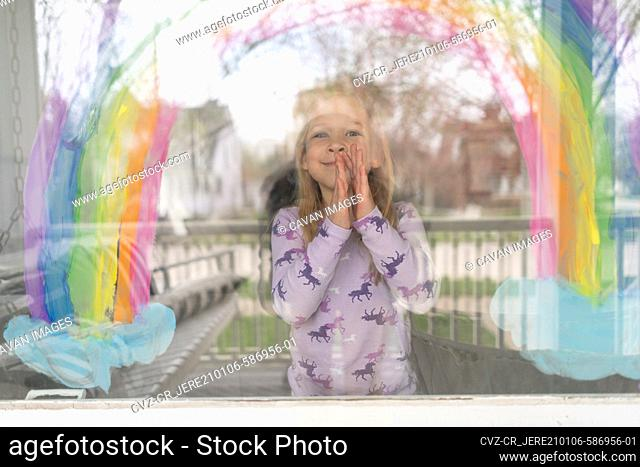 outside in view of cute girl under rainbow painted on window