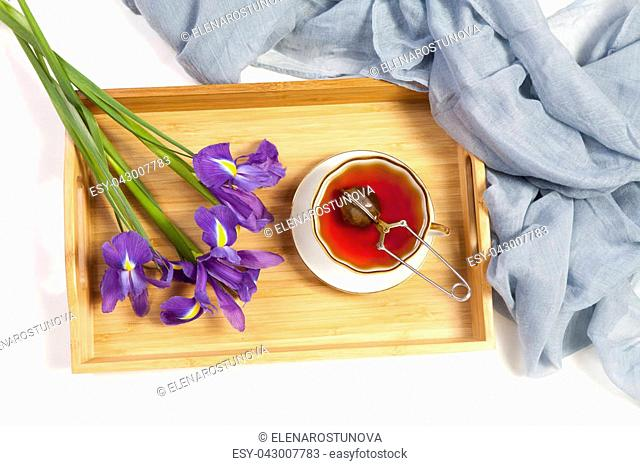 Violet Irises xiphium (Bulbous iris, sibirica) with cup of tea on white background with space for text. Top view, flat . Holiday greeting card for Valentine's...