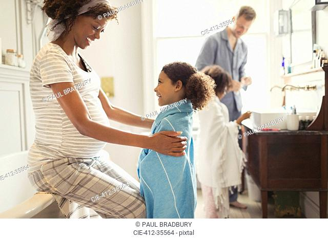 Pregnant mother wrapping towel on daughter after bath time