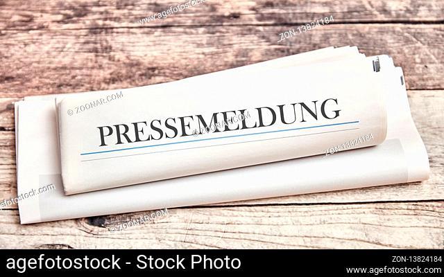 Pressemeldung oder Pressemitteilung als gefaltete Zeitung auf einem Tisch