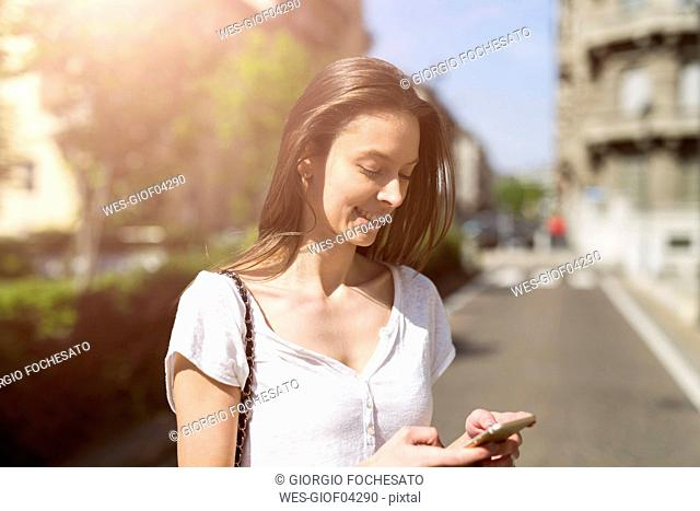 Smiling young woman looking at cell phone in the city