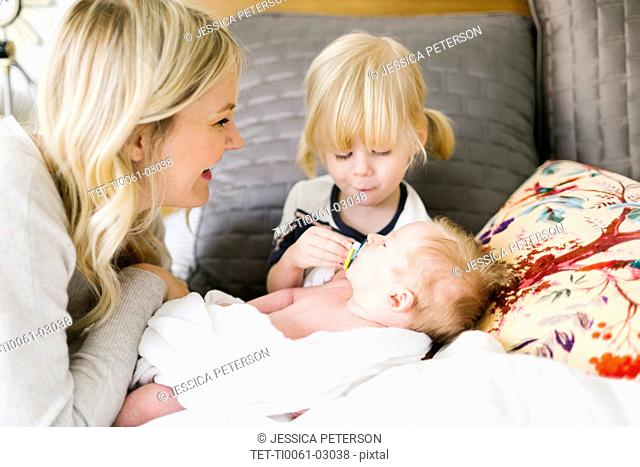 Woman playing with her children on bed