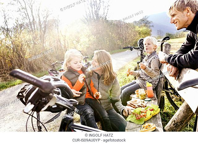 Family with bicycles resting on bench by roadside eating picnic smiling