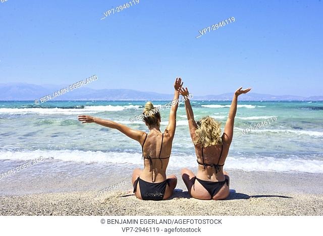 best friends, two vital girls sitting in bikini on beach and looking at sea. Dutch ethnicity. At holiday destination Chrissi Island, Crete, Greece