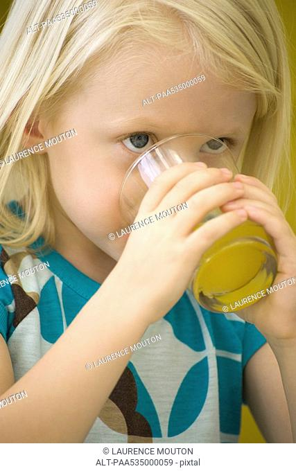 Little girl drinking glass of juice, close-up