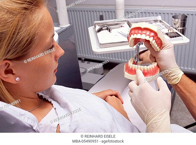 Dentist declares tooth problems at the model to his patient