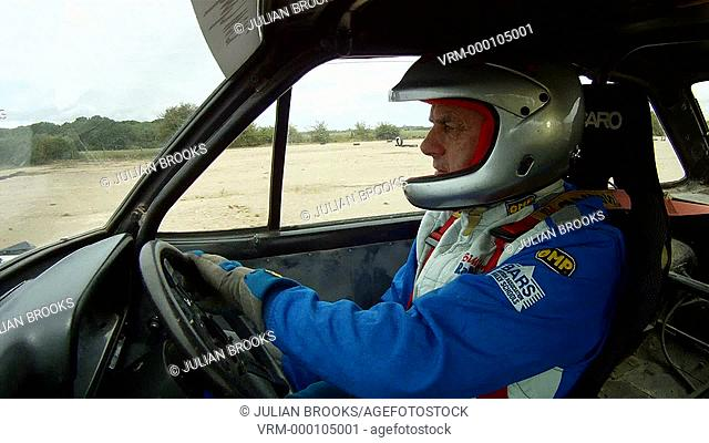 Rally driver demonstrating cornering technique from inside the car