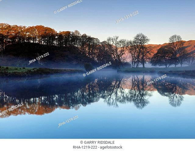 Dawn light reveals the autumn colour of trees and distant fells with mist lying above Elterwater revealing a perfect reflection, Lake District National Park