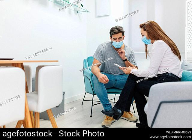 Doctor and patient wearing face mask using digital tablet while sitting at office