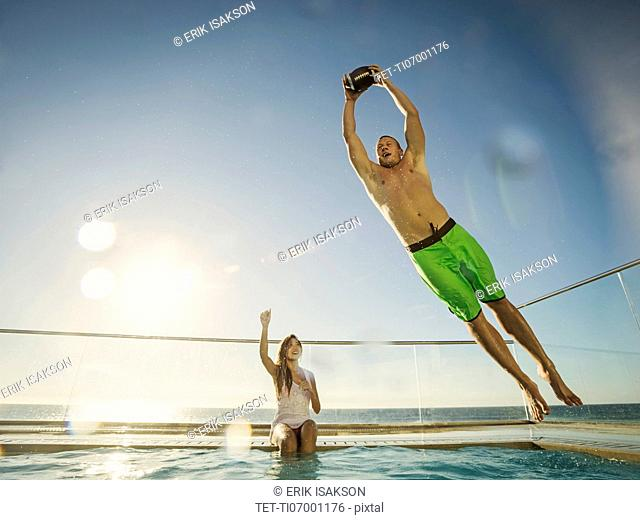 Couple playing football in swimming pool