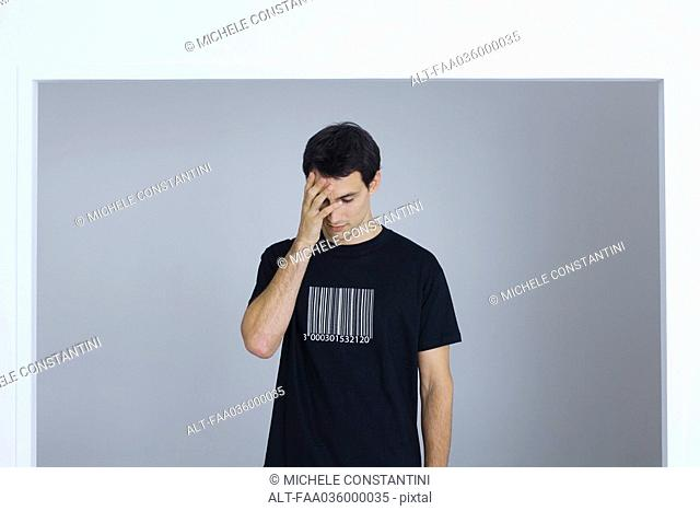 Man wearing tee-shirt printed with bar code, covering face with hand