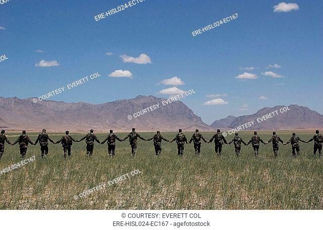 Afghanistan National Army Soldiers form a line while participating in an unexploded ordinance field training exercise conducted by U.S. Army