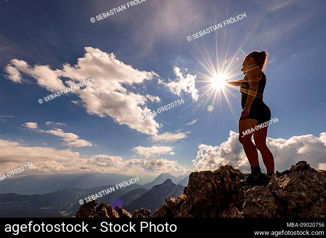 Young woman in backlight on the mountain