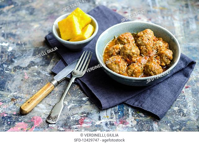Beef meatballs in a rich tomato sauce with herbs in a blue bowl with cutlery knife and fork on a blue napkin with polenta squares