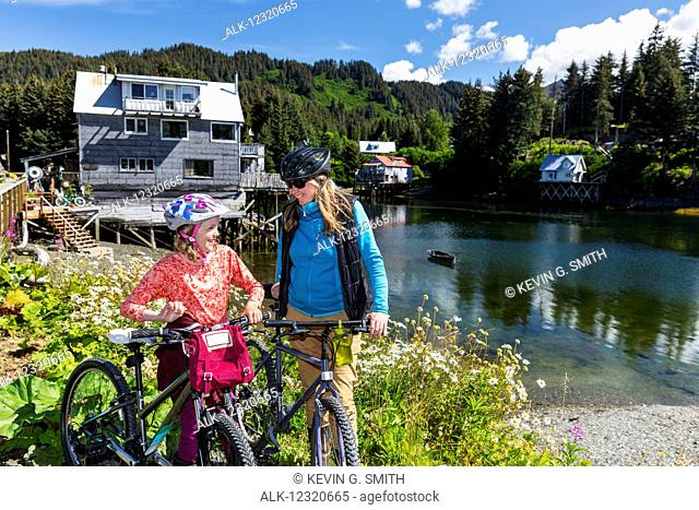 Mother and daughter with bicycles next to the Seldovia Slough on a sunny day, Southcentral Alaska, USA