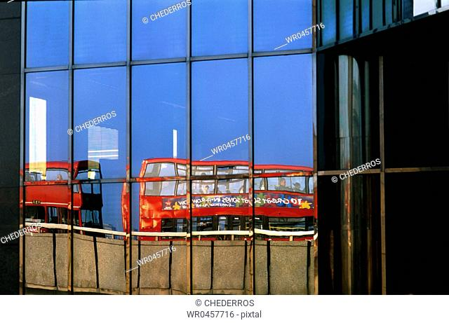 Reflection of double-decker buses on the glass front of a building, London, England