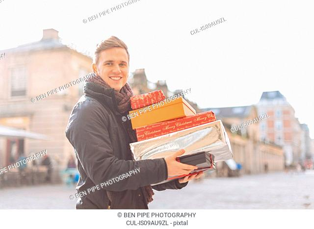 Portrait of young man carrying stack of xmas presents in Covent Garden, London, UK