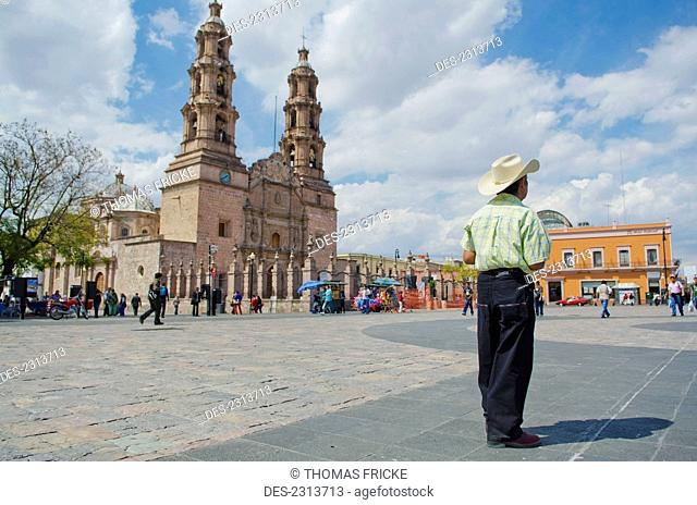 Mexico, Aguascalientes State, Man Wearing Cowboy Hat Standing In Large City Plaza Beside Large Cathedral; Aguascalientes