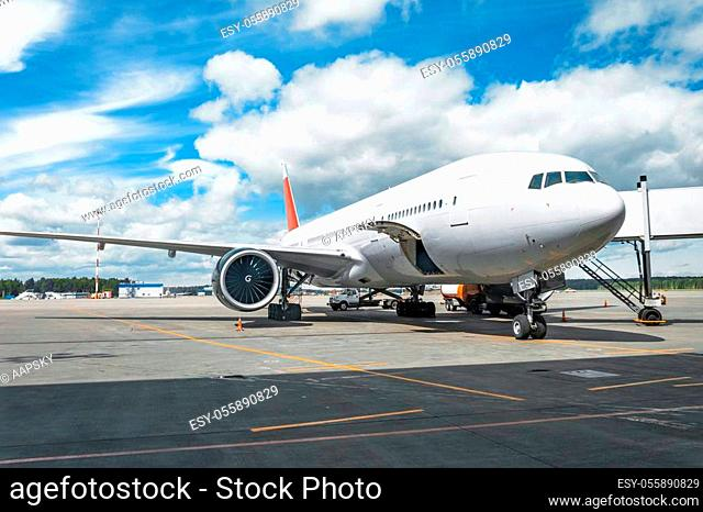 Passenger aircraft with boarding stairs, waiting for boarding passengers and baggage before the flight, summer airport trip