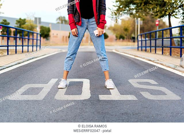 Crop view of young woman with mobile phone standing on the word 'stop' on the street