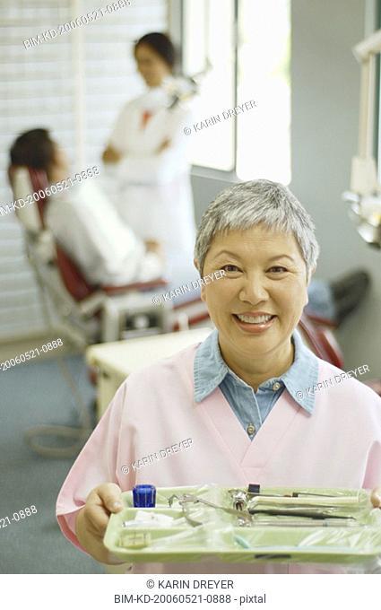 Senior Asian female dental assistant smiling