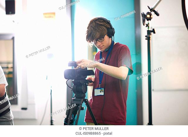 Young male college student filming in TV studio