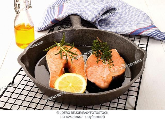 raw salmon steak with lemon, thyme and rosemary in a cast iron pan