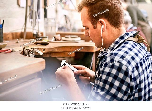 Male jeweler using calipers and listening to music with headphones in workshop