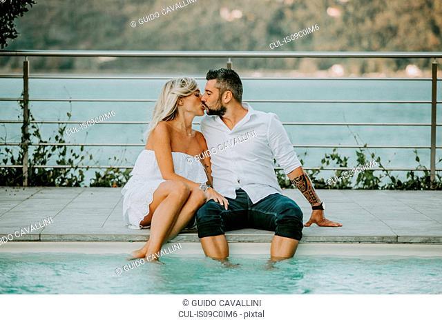 Romantic mid adult couple kissing on poolside, Stresa, Piemonte, Italy