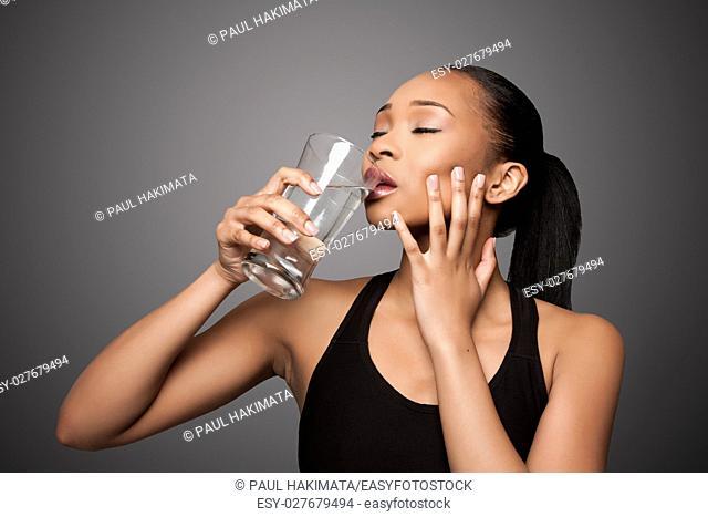 Beautiful healthy black asian woman enjoying drinking glass of water