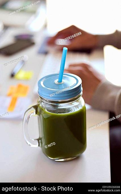 closeup of a green detox smoothie served in a glass jar on an office desk, and a young caucasian man using his computer in the background