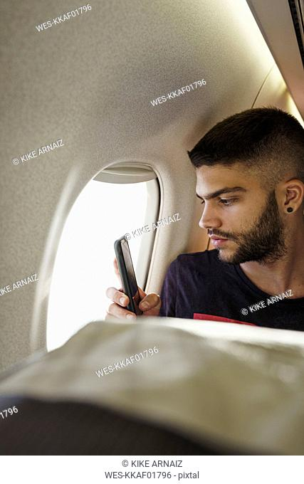 Young man in a plane with cell phone