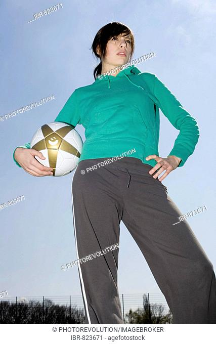 Young woman standing on a sports field, holding a football