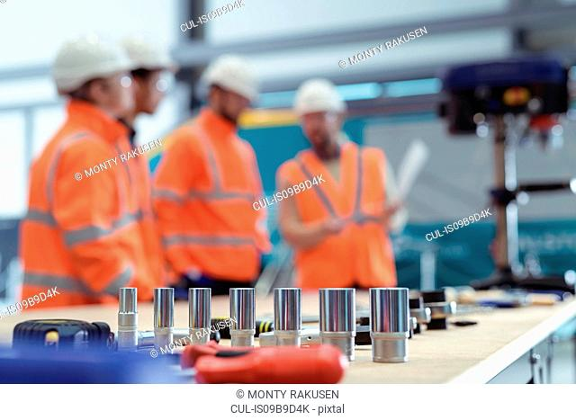 Defocussed view of group of apprentices with instructor at railway engineering facility