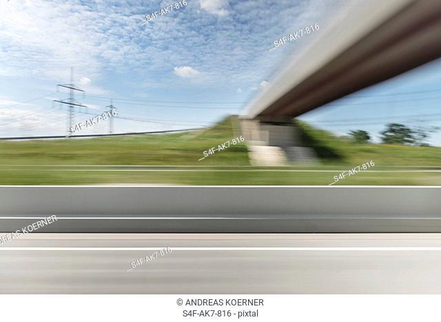 Überlandleitungen und Brücke über einer Autobahn