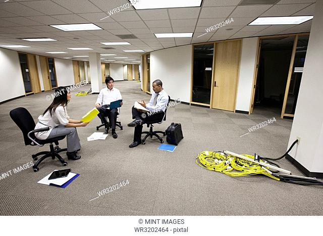 A mixed race group of three business people sitting in an open space and making plans for a new office layout