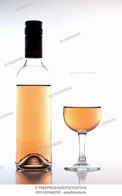 Rose wine glass and bottle on white background, France