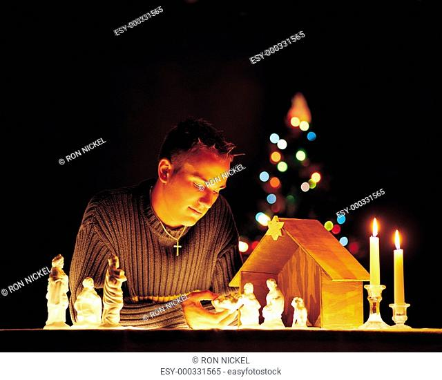 Man with nativity scene figurines and lights
