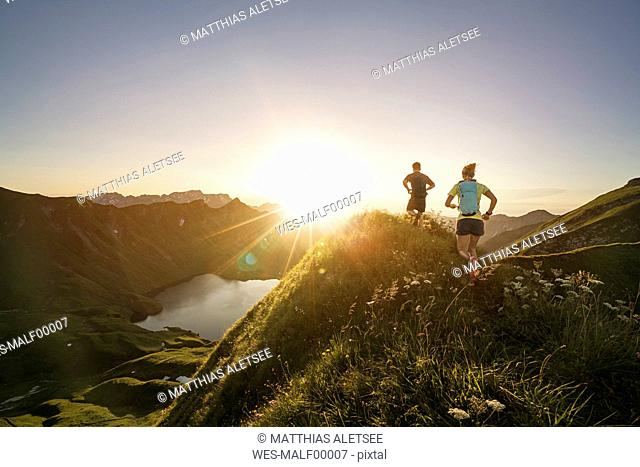 Germany, Allgaeu Alps, man and woman running on mountain trail