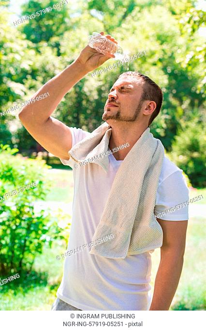Sport fitness man. Young athletic man cooling himself after training by squirting water over himself from a drinks bottle outdoors at park