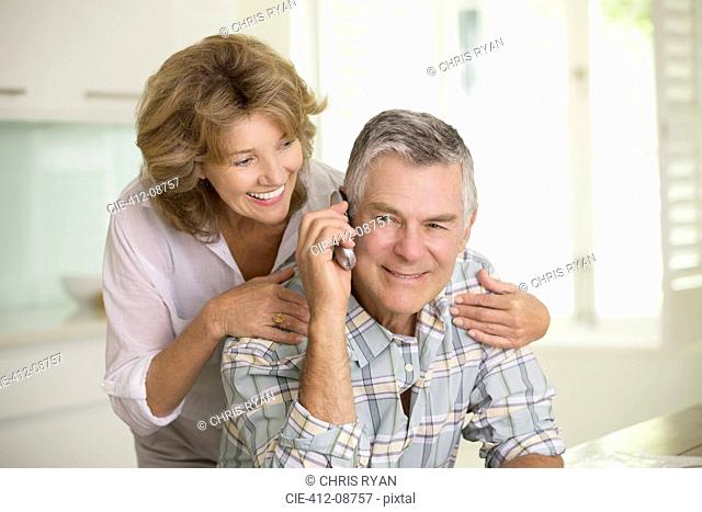 Senior couple talking on telephone
