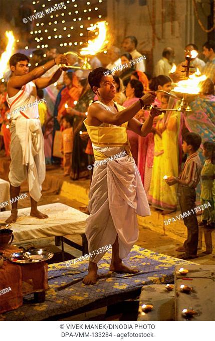 Young priest performing ganga pooja at ghat on banks of holy Ganga river ; Varanasi ; Uttar Pradesh ; India