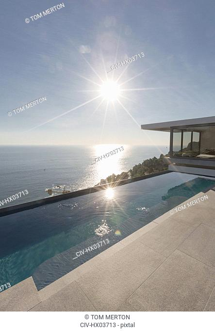 View of sun shining over ocean and modern, luxury home showcase exterior lap pool patio
