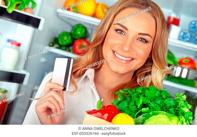Healthy nutrition concept, portrait of a beautiful young woman standing near open refrigerator with a full paper bag of a fresh vegetables, holding credit card