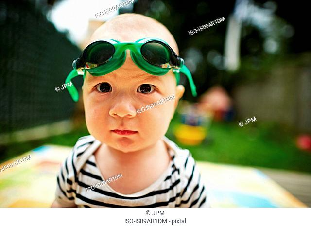 Close up portrait of baby boy looking at camera wearing swimming goggles
