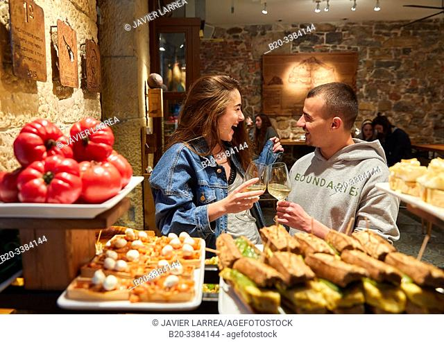 "Young couple eating ""Pintxos"" at the Meson Portaletas, Parte Vieja, Old town, Donostia, San Sebastian, Gipuzkoa, Basque Country, Spain"