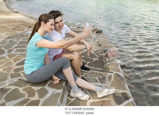 Loving couple taking selfie while sitting at lake in town